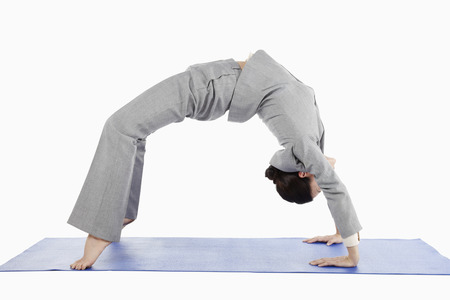 backwards: Mid adult businesswoman bending backwards in yoga position