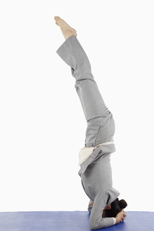 headstand: Mid adult businesswoman doing a bound headstand