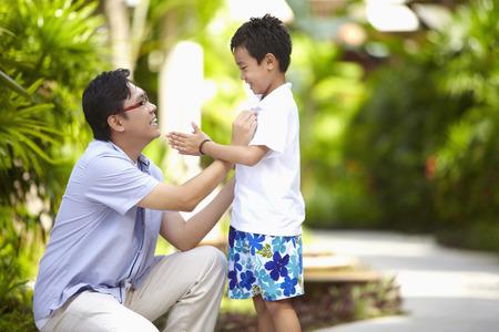 Man adjusting sons shirt