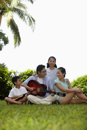 man playing guitar: Man playing guitar for his family in the park