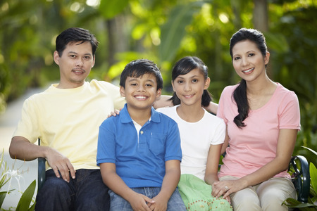 malay boy: Family sitting together on a bench LANG_EVOIMAGES