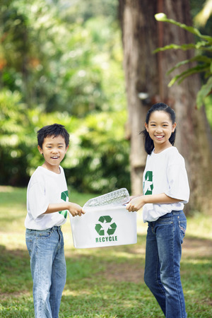recycling bin: Boy and girl carrying recycling bin