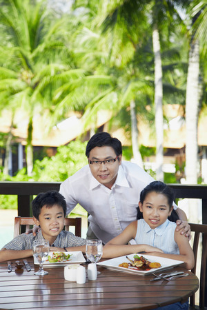 family: Man having lunch together with son and daughter LANG_EVOIMAGES