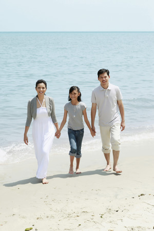 holding hands while walking: Family holding hands while walking on the beach LANG_EVOIMAGES