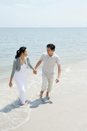 holding hands while walking: Man and woman holding hands while walking on the beach