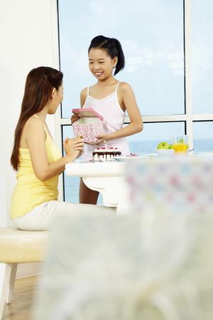 cadeau anniversaire: Fille donnant maman un cadeau d'anniversaire surprise