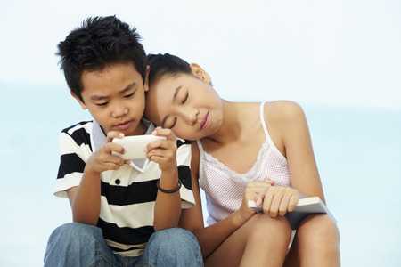 head and shoulder: Boy playing game on mobile phone while girl resting head on his shoulder