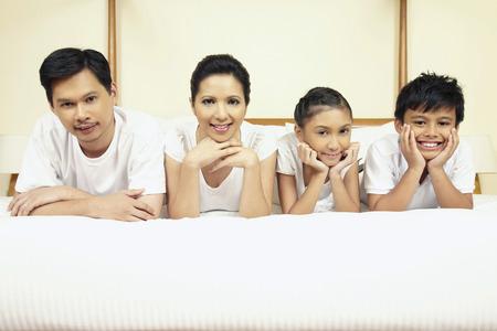 viendo television: Familia viendo la televisi�n juntos en la cama
