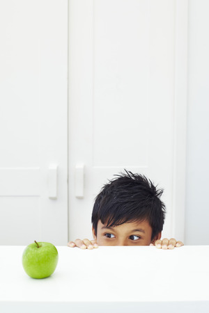 peeking: Boy appearing from under the table, peeking at green apple