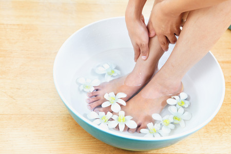 soaking: Feet in a bowl of water with flowers