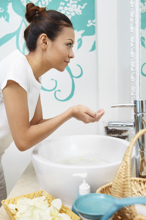 woman washing face: Woman washing face in the bathroom