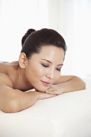 lying forward: Woman lying forward on massage table with her eyes closed