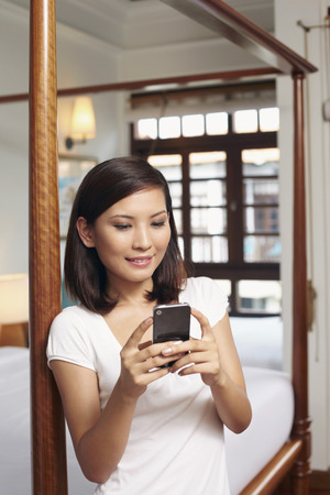 text messaging: Woman text messaging on mobile phone LANG_EVOIMAGES