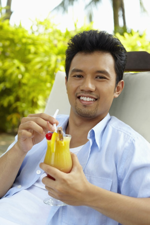 reclining chair: Man reclining on lounge chair with a glass of fruit juice