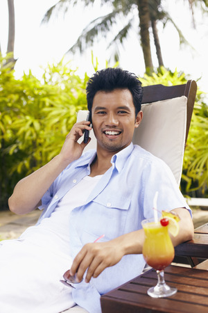 reclining chair: Man talking on mobile phone while reclining on lounge chair