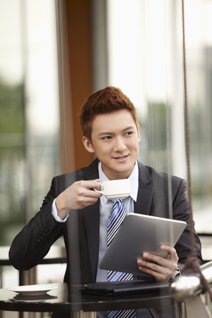 business: Businessman using digital tablet while drinking coffee