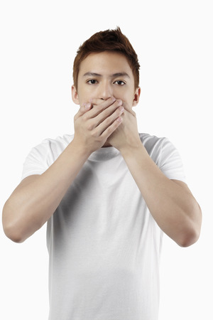 Man covering his ears depicting the quote Speak No Evil Stock Photo