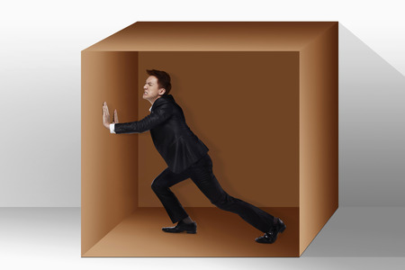 trapped: Businessman trapped inside a box, pushing against it