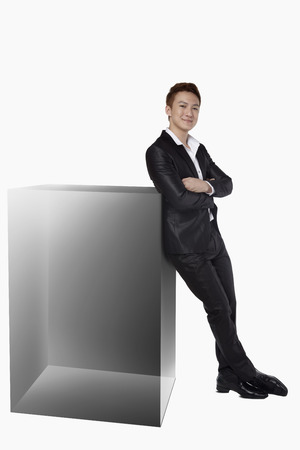 leaning against: Businessman leaning against a square cube