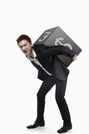 money matters: Businessman lifting a cube on his back with currency signs