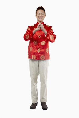 clasped hand: Man in traditional clothing with hand clasped wishing Happy Chinese New Year
