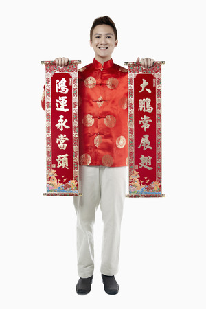 traditional clothing: Man in traditional clothing holding banner with Chinese New Year greetings