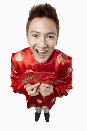 packets: Man in traditional clothing holding red packets