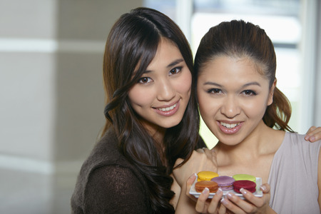two people only: Women with a plate of macaroons