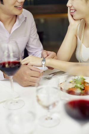 wrist watch: Man putting on wrist watch for woman