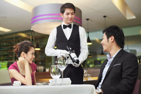 Waiter serving wine to man and woman Stock Photo
