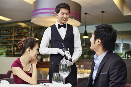 serving: Waiter serving wine to man and woman LANG_EVOIMAGES