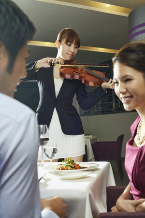 only three people: Man and woman in a restaurant with violinist playing in the background.  LANG_EVOIMAGES