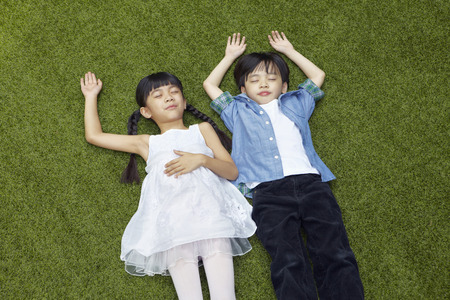 Boy and girl lying on the grass Stock Photo