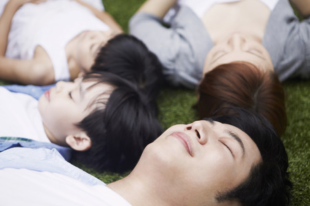 Family lying down on the grass Stock Photo
