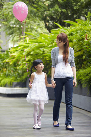 one parent: Mother and daughter walking hand in hand LANG_EVOIMAGES