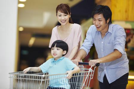 empujando: Los padres empujando hijo en un carrito de la compra