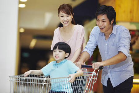 Parents pushing son in a shopping cart