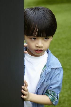 shyness: Boy standing behind a pillar