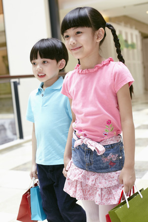 Boy and girl carrying shopping items
