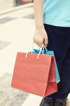 waist down: Waist down shot of a boy carrying shopping items