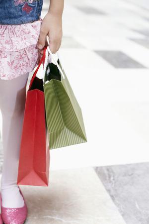 waist down: Waist down shot of a girl carrying shopping items