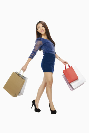 spending full: Woman walking and posing  while carrying shopping bags LANG_EVOIMAGES