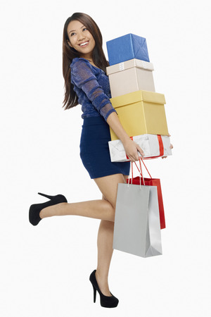 spending full: Woman posing with shopping bags and a stack of boxes LANG_EVOIMAGES