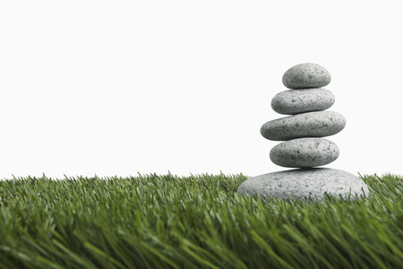 stacked up: Five stones stacked up on grass