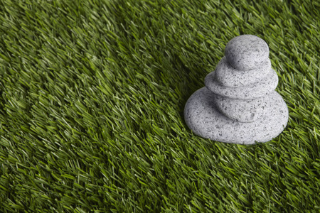 five objects: Five stones stacked up on grass