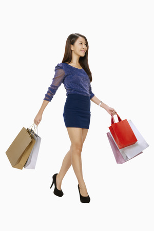 spending full: Woman walking while carrying shopping bags LANG_EVOIMAGES