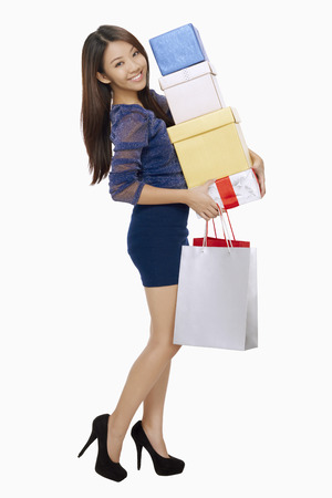 spending full: Woman with posing shopping bags and a stack of boxes