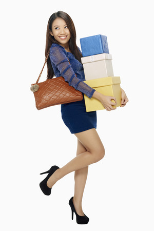 spending full: Woman posing and carrying a stack of boxes