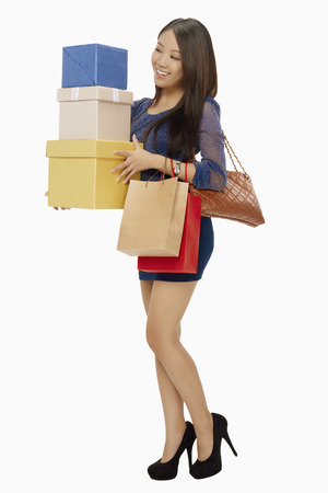 spending full: Woman carrying shopping bags and boxes LANG_EVOIMAGES