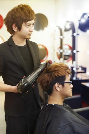 hair stylist: Stylist blow-drying customers hair